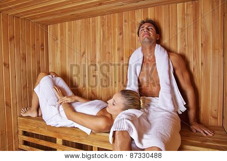 Happy couple sitting and laying relaxed in hotel sauna