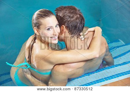 Smiling couple sitting in hotel swimming pool in summer