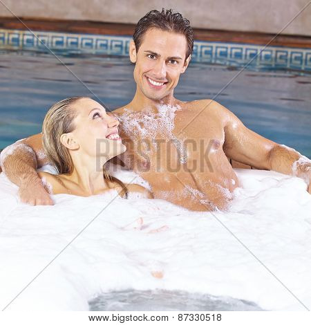 Happy couple taking foam bubble bath in a hotel whirlpool