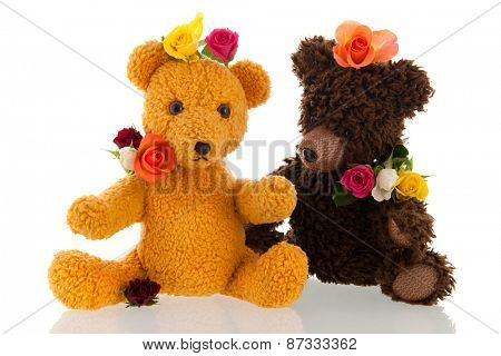Stuffed hand made bears with colorful flowers isolated over white background