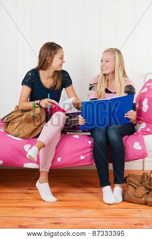 two teengirls sitting on bed making homework together