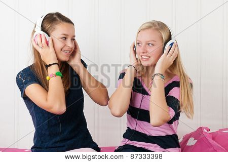 Two teenager girls listening to music with headphones