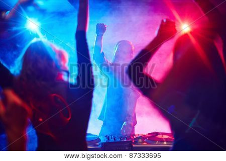 Excited deejay and dancing crowd enjoying disco party in nightclub
