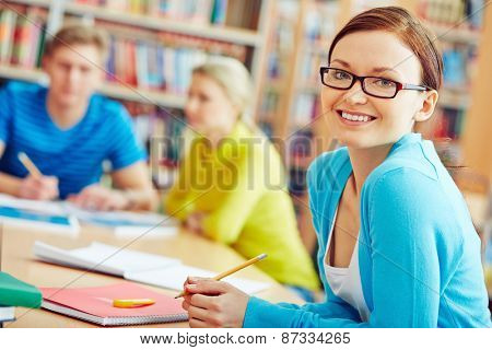 Female student sitting in college library and looking at camera
