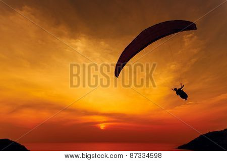 Paraglider silhouette against the background of the sunset sky and sea