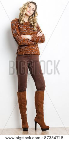 standing woman wearing brown clothes and boots