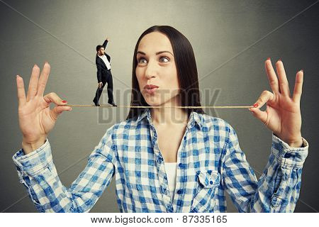 amazed woman looking at small man on the rope over dark background