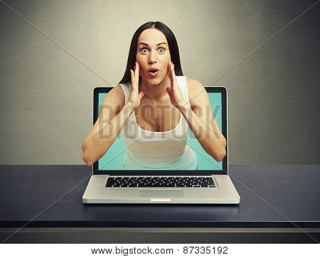 amazed woman got out of the laptop against dark background