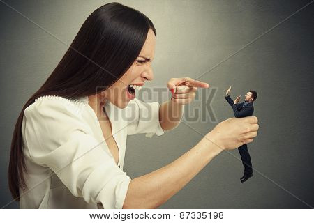 emotional woman holding in hand small scared man, pointing at him and yelling. photo over dark background