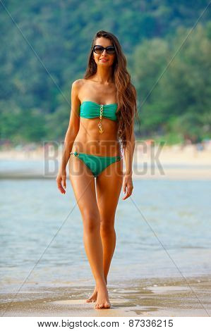 tanned brunette walking along the beach