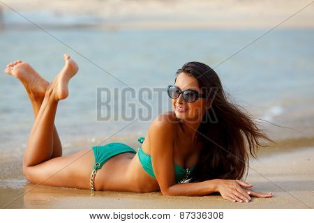 tanned brunette laying on the beach