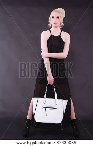 Young blond woman with white bag