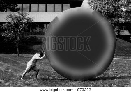 Man Push A Huge Circle (Black And White)