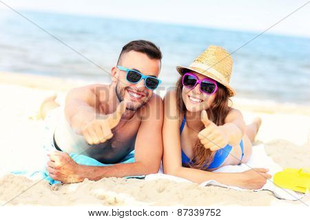 A picture of a happy couple lying on the beach and showing ok signs