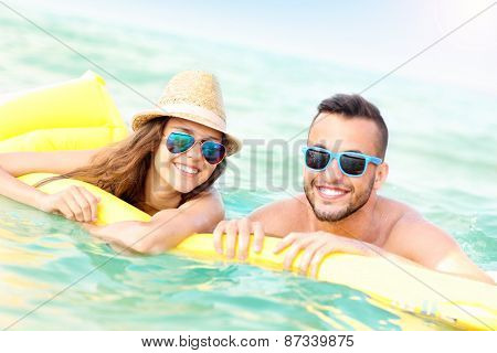 A picture of a young couple having fun on a matress in the Baltic Sea