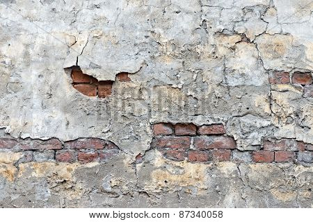 Old Brick Wall With The Peeled Plaster