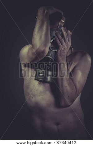 Fear, concept of risk of contamination, naked man with gas mask