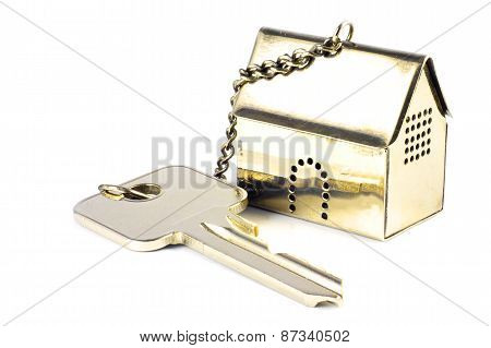 House Key With A Golden Model House As Keychain, Isolated On White