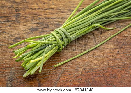 bunch of fresh green chives against rustic grunge wood