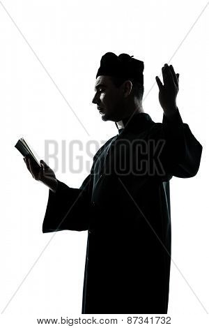 one  man priest reading bible silhouette in studio isolated on white background