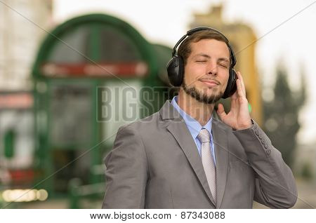 young stylish handsome man wearing headphones in the city