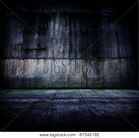 Huge grungy concrete room, in darkness.