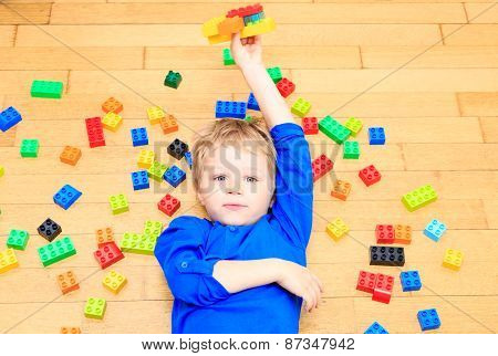 child playing with colorful plastic blocks indoor