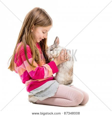 little girl in a crimson sweater  with baby rabbit over white background