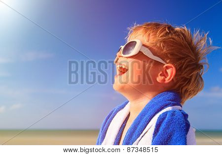 happy little boy laugh wrapped in beach towel on sky