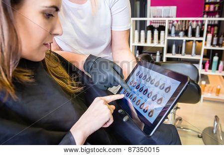 Woman choosing new color in hair dye palette on tablet