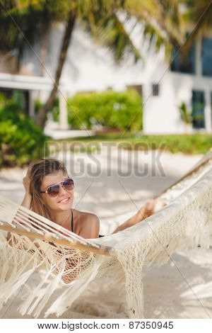 fashion portrait of sexy girl in bikini lying at beach