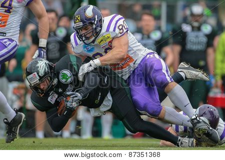 VIENNA, AUSTRIA - APRIL 13, 2014: WR Georg Pongratz (#86 Dragons) is tackled by DL Alexander Taheri (#90 Vikings).