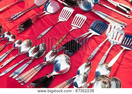 tableware and kitchenware concept - spoons and spatulas sale at street market