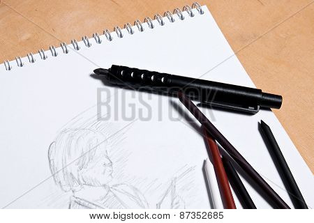Clutch Pencil With Notebook On A Wooden Background.