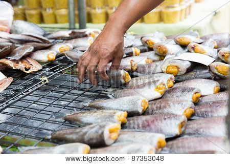 cooking, asian kitchen, sale and food concept - close up of hand taking fish at street market