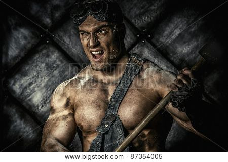 Strong aggressive coal miner with a hammer over dark grunge background. Mining industry. Art concept.