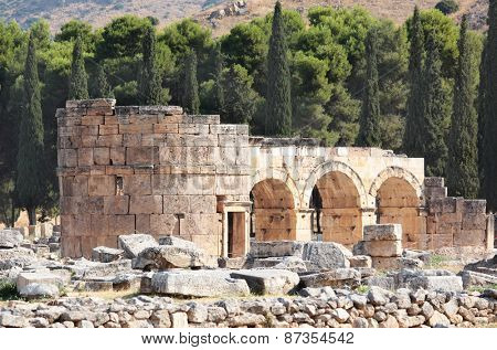 PAMUKKALE, TURKEY - AUGUST 18, 2011: Domitian gate of the ancient city of Hierapolis. Since 1988, the archaeological site and nearby travertine terraces are listed as UNESCO World Heritage site