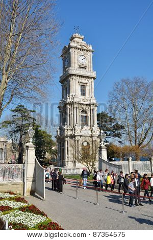 ISTANBUL, TURKEY - MARCH 22, 2014: Tourists visiting Dolmabahce palace against the clock tower. The tower was designed by the sultan's court architect Sarkis Balyan in 1890-1895
