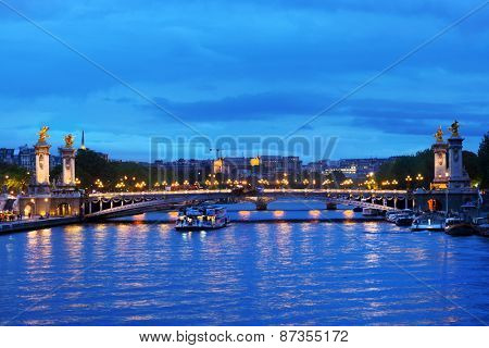 PARIS, FRANCE - SEPTEMBER 12, 2013: Trip boat on the Seine under the Pont Alexandre III. This bridge is widely considered as the most ornate in Paris