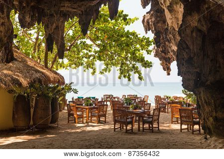leisure, travel and tourism concept - view to open-air restaurant on beach resort from cave