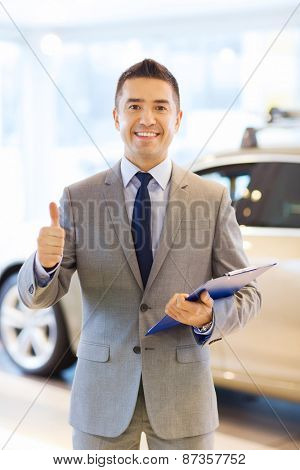 auto business, car sale, consumerism, gesture and people concept - happy man with clipboard showing thumbs up at auto show or salon
