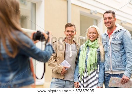 travel, vacation, technology and friendship concept - girl picturing group of friends with map and city guide in city