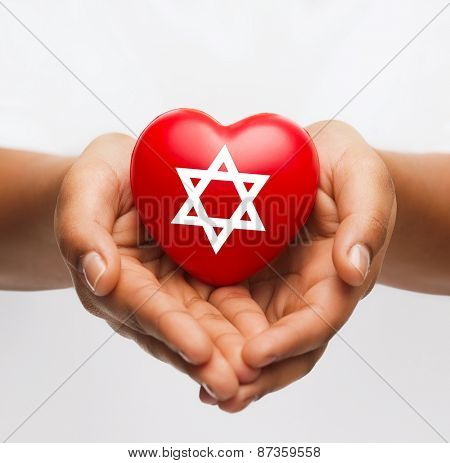 religion, christianity and charity concept - african american female hands holding red heart with star of david symbol
