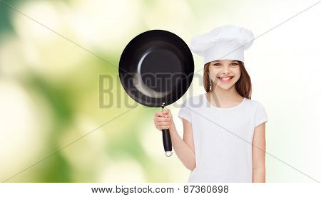 advertising, childhood, cooking and people - smiling girl in white t-shirt and cooking hat holding pan over green background