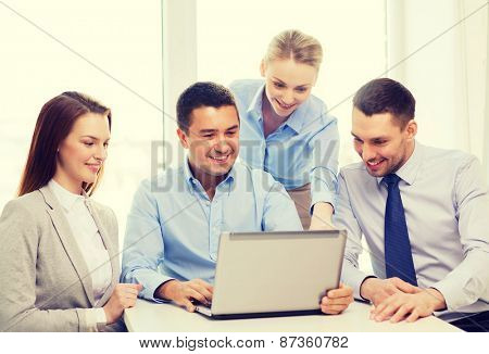 business, teamwork and office concept - smiling business team working with laptop computer in office