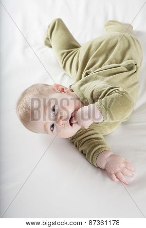 Baby Lying Twisted Looking At Camera