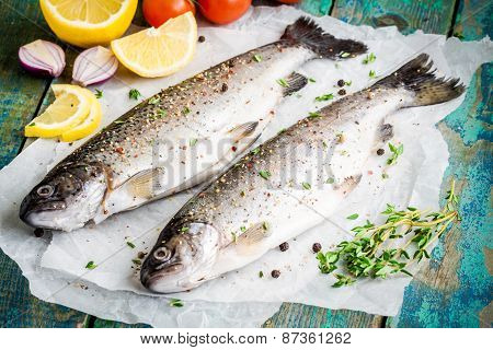 Two Raw trouts On Paper With Thyme, Peppers And Lemon