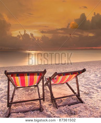Couples Of Wood Chairs Beach At Sea Side And Parashoot Ship Playing Over Sun Set Sky