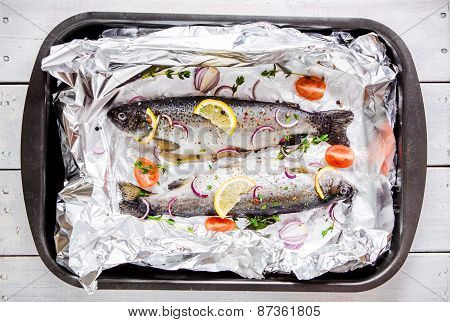 Two Raw River trouts With Thyme, Lemon, Red Onion And Tomatoes In Foil