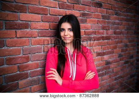 Portrait of a happy woman with arms folded standing over brick wall. Looking at camera. Wearing in red sportive jacket